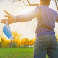 Ihminen ulkona maski kädessä levittää kädet auringon edessä